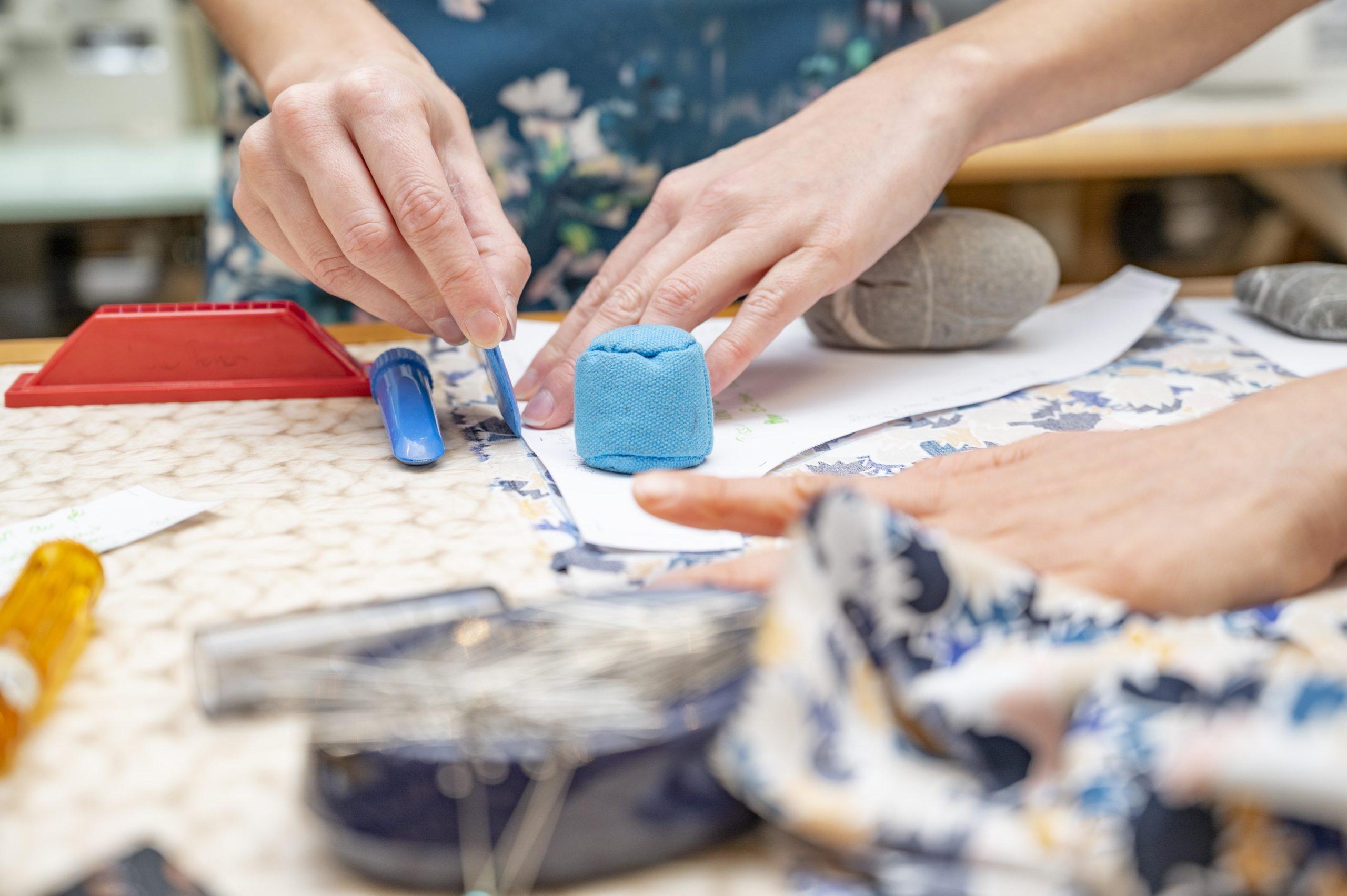 Personnes en train de créer un vêtement et tracer sur du tissu pendant un cours de couture à Nice