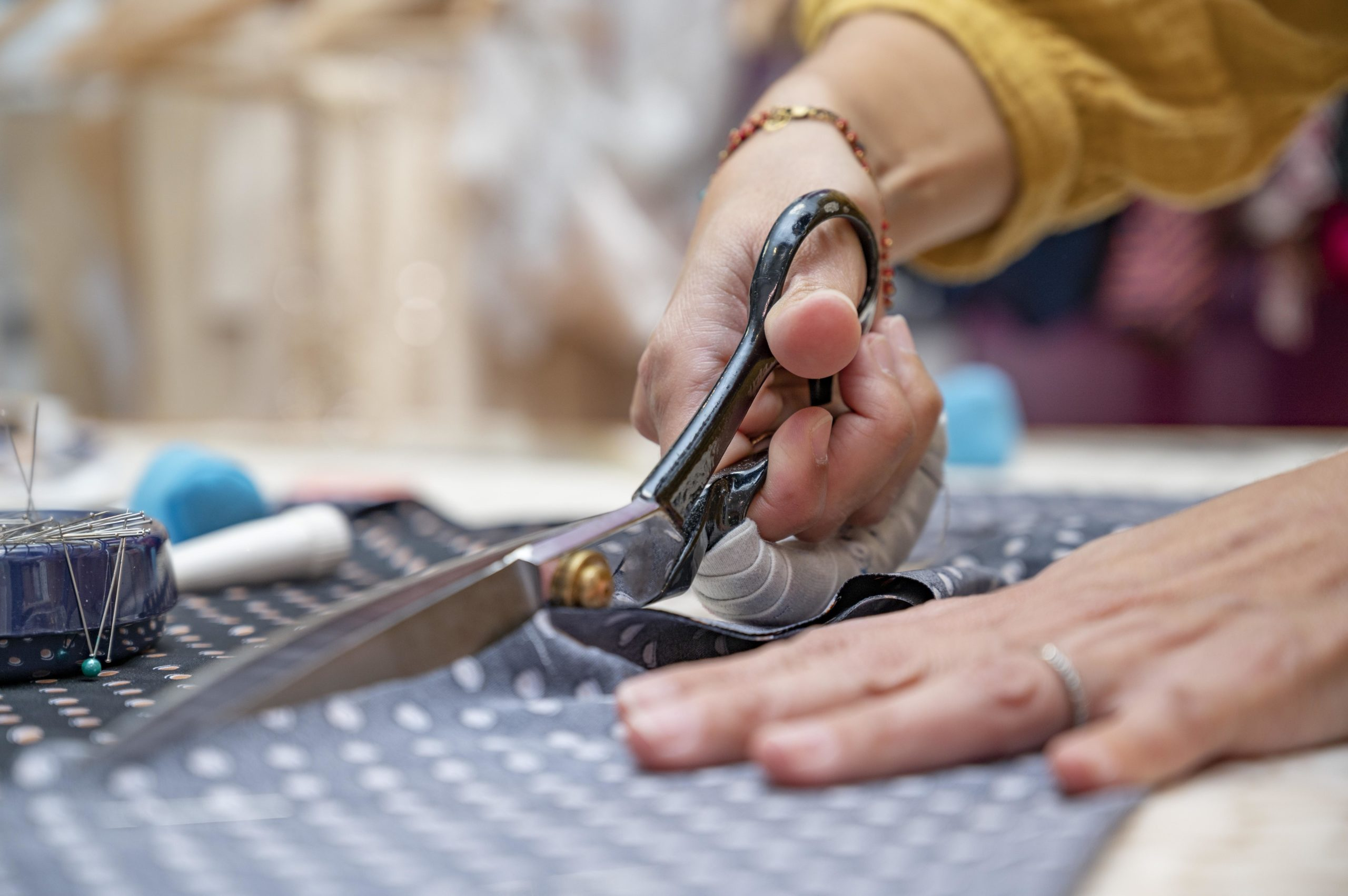 Personne qui coupe du tissu avec des ciseaux tailleur pendant un cour de couture sur la Côte D'azur